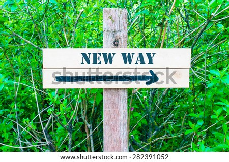 NEW WAY written on Directional wooden sign with arrow pointing to the right against green leaves background. Concept image with available copy space - stock photo