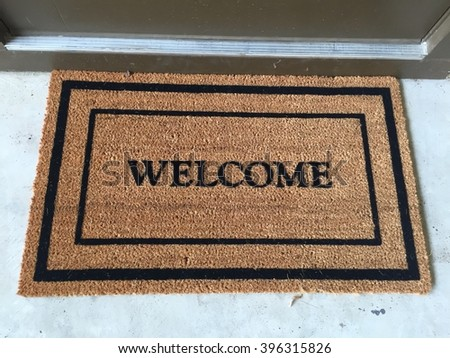 """New """"Welcome"""" may with black trim laying in front of a door. - stock photo"""