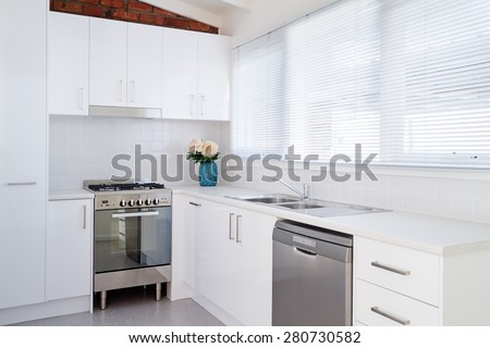 New white kitchen and appliances in a renovated villa unit - stock photo