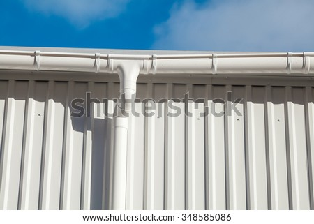 New white rain gutter on a building with white metal sheet against blue sky - stock photo