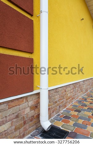 New white rain gutter on yellow wall - stock photo