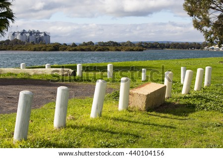 New white traffic bollards  in  the green lawn  open space near the Leschenault Estuary foreshore in Bunbury, Western Australia on a sunny afternoon in early winter.