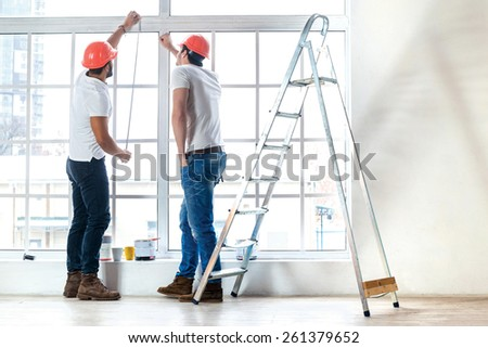 New windows, moving and repair in the apartment. Two workers make measurements of windows and repairs in a new apartment while ladder stands in an empty apartment. - stock photo
