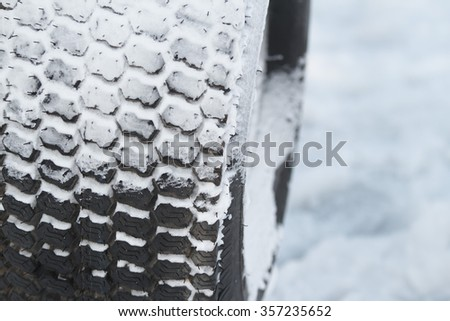 New winter car tire in fluffy snow - stock photo