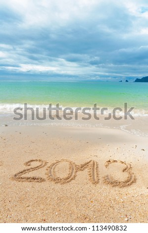 New year 2013 and Christmas beach vacation and holiday concept. 2013 written on tropical beach sand, vertical image - stock photo
