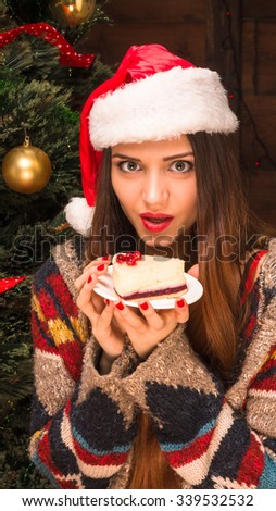 New Year and Christmas concepts. Beautiful girl holding a delicious piece of cake on the plate and looking at the camera with excitement.