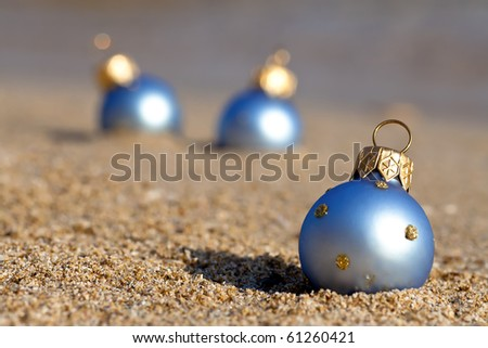 New year at the beach! Christmas ornaments standing in the sand near the water
