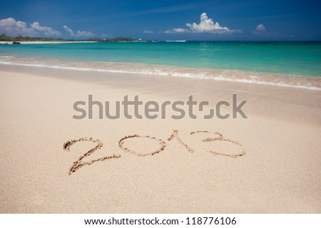 """New year background of beach with """"2013"""" handwritten in the sand, holiday christmas concept - stock photo"""