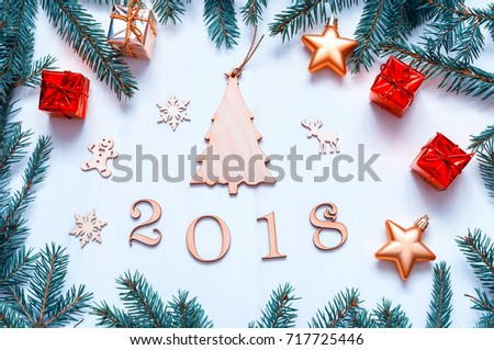 New Year 2018 background with figures, Christmas toys, with frame of blue fir branches. New Year 2018 composition. Flat lay, top view of New Year 2018 festive still life