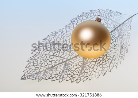 New Year background with golden glass toy on silver decorative leaf - stock photo