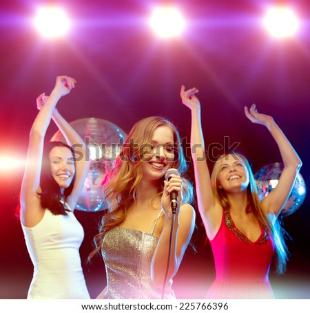 new year, celebration, friends, bachelorette party, birthday concept - three women in evening dresses dancing and singing karaoke - stock photo