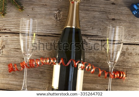 New Year. Christmas. Celebration, Champagne in a glass bottle and wine glass,, tree, bells, serpentine. Top view, closeup. - stock photo