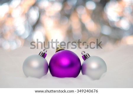 NEW YEAR, CHRISTMAS: Three Purple and Silver Merry Christmas Balls with Bokeh Background