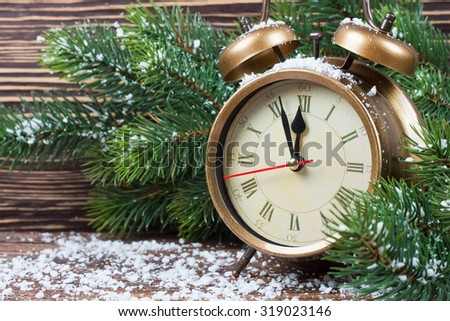 New Year clock and fir branch with snow flakes - stock photo