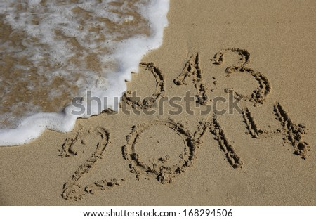 New Year 2014 coming concept, written on a beach with wave - stock photo