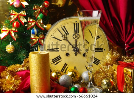 New Year composition with old clock, candle  and glass of champagne