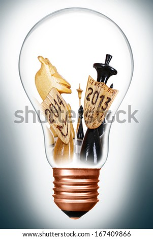 New Year concept. Chess battlefield between 2013 and 2014 years in lightbulb - stock photo