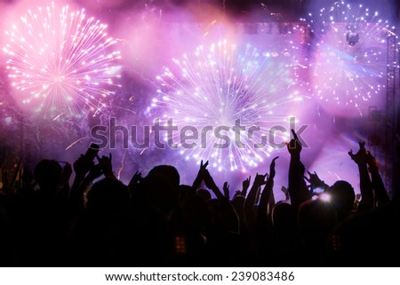 New Year concept - fireworks and cheering crowd celebrating the New year - stock photo