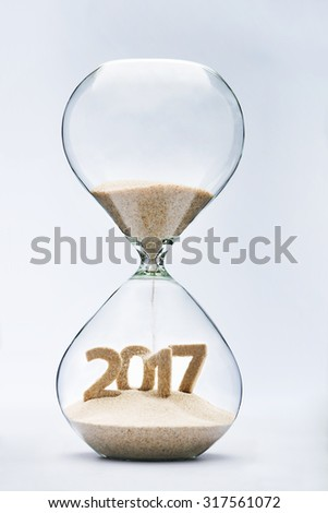 New Year 2017 concept with hourglass falling sand taking the shape of a 2017