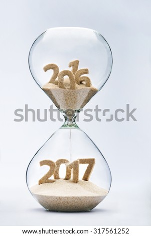 New Year 2016 concept with hourglass falling sand taking the shape of a 2017 - stock photo
