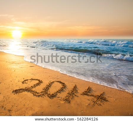 new year 2014 digits on ocean beach sand - stock photo