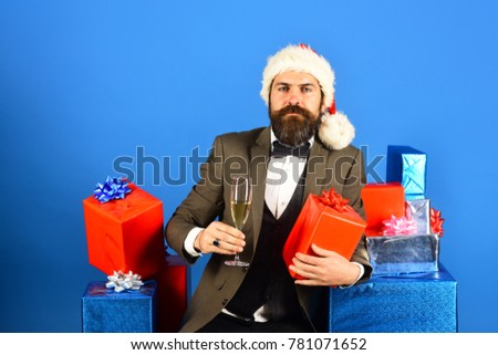 New year eve concept. Santa in retro suit presents blue and red gifts. Man with beard holds present and champagne. Businessman with serious face holding boxes pile and drink on blue background