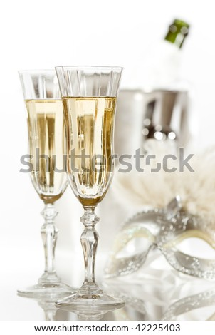 New Year fancy dress party with glasses of champagne and masquerade mask in high key - stock photo