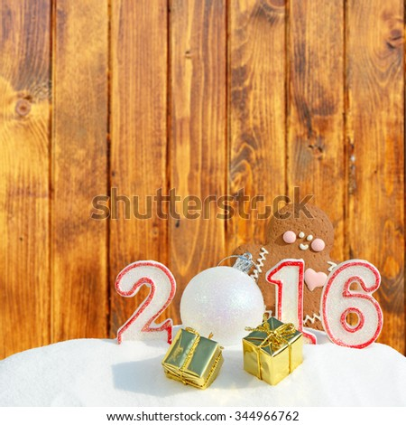 New Year 2016. Figure 2016, Christmas balls, gifts and gingerbread man on wooden background - stock photo