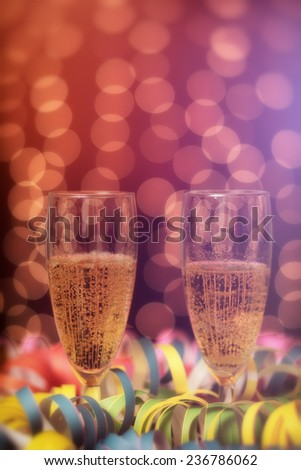 New Year / Glasses full of champagne, party lights in the background - stock photo