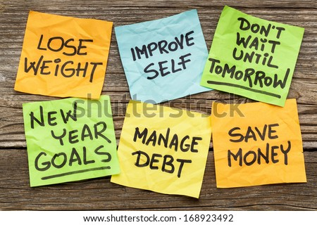 New Year goals or resolutions - handwriting on sticky notes against grained wood - stock photo