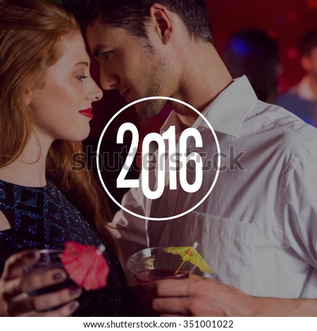 New year graphic against cute couple drinking cocktails together - stock photo