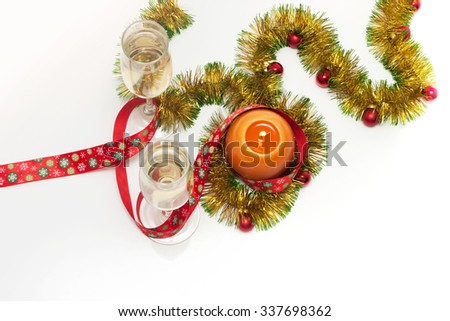 New year greeting card template made of golden and green tinsel with red christmas balls, red ribbon, orange candle and two glasses of champagne with copy space, top view - stock photo