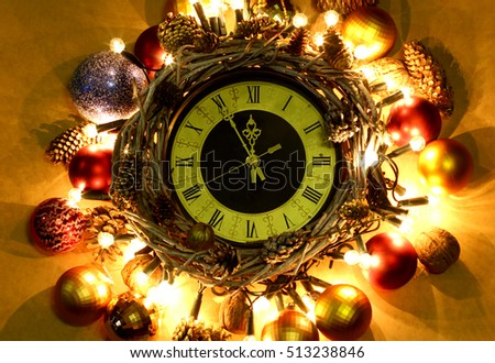 New Year hand made Concept. Time five minutes of Twelve O'clock Midnight. Christmas clock in wreath and garlands of colored light bulbs with craft decorations.