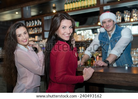 New Year in a bar with beer. Young beautiful bartender is wearing New Year Santa Claus hat and giving cocktails to two girls standing in front of him. Merry Christmas and happy New Year in a pub