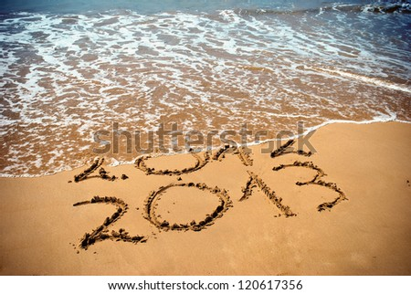 New Year 2013 is coming concept - inscription 2012 and 2013 on a beach sand, the wave is covering digits 2012 - stock photo