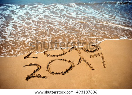 New Year 2017 is coming concept - inscription 2017 and 2016 on a beach sand, the wave is covering digits 2016. New Year 2017 celebration on New Year tropical island travel tour.