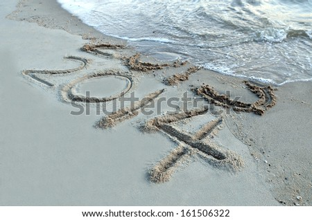 New Year 2014 is coming concept - inscription 2013 and 2014 on a beach sand, the wave is starting to cover the digits 2013  - stock photo