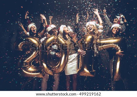 New 2017 Year is coming! Group of cheerful young people in Santa hats carrying gold colored numbers and throwing confetti
