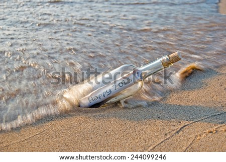 New Year 2016 message in a bottle on the beach - stock photo