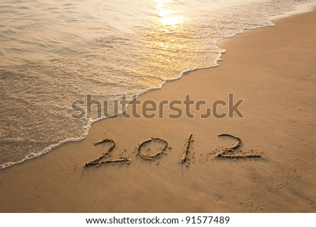 new year message on the sand beach - stock photo