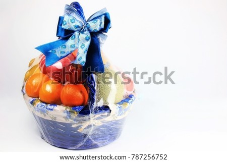 New year mix fruity in wrapped blue basket decorating by blue pattern fabric ribbon bow on copy space white background