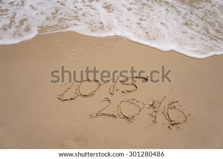 new year numbers 2015 and 2016  drawings in the sand on the beach