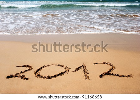 New year 2012 on wet golden beach sand in front of the ocean - stock photo