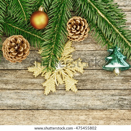 New Year or Christmas background: fir branches, colorful glass balls and golden snow-flake, cones over old wooden backdrop, top view, copy space, tinted photo