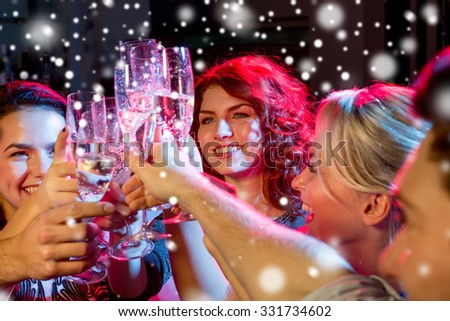 new year party, holidays, celebration, nightlife and people concept - smiling friends with glasses of non-alcoholic champagne in club and snow effect - stock photo