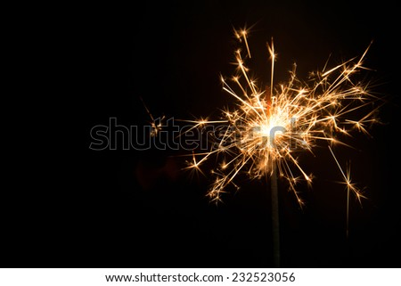 New year party sparkler on black background - stock photo