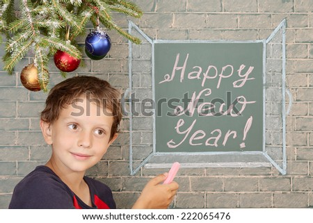 New Year perspectives. Christmas decoration, smiling boy and message on chalkboard: Happy New Year! - stock photo