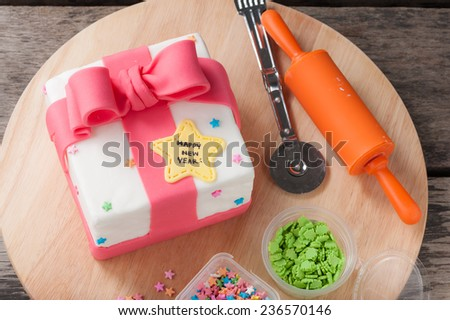 New year present concept fondant cake on wood table. - stock photo