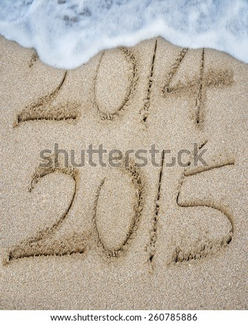 New year 2015 replace 2014 on sand beach background - stock photo