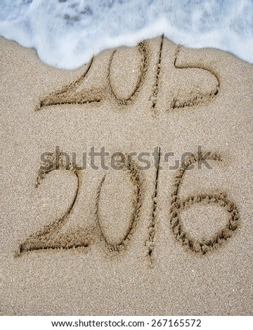 New year 2016 replace 2015 on sand beach background - stock photo